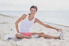 Happy healthy woman smiling while doing leg stretching stock photo