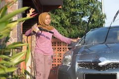 Portrait of happy hijab women car cleaning - Removing the soap with water, using a garden hose and a spray gun. Portrait of happy hijab woman doing car cleaning royalty free stock photos