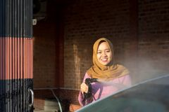 Portrait of happy hijab women car cleaning - Removing the soap with water, using a garden hose and a spray gun. Portrait of happy independent hijab woman doing royalty free stock photography