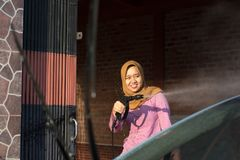 Portrait of happy hijab women car cleaning - Removing the soap with water, using a garden hose and a spray gun. Portrait of happy independent hijab woman doing royalty free stock photo