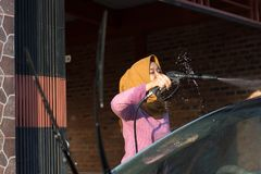 Portrait of happy hijab women car cleaning - Removing the soap with water, using a garden hose and a spray gun. Portrait of happy hijab woman doing car cleaning royalty free stock images