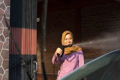 Portrait of happy hijab women car cleaning - Removing the soap with water, using a garden hose and a spray gun. Portrait of happy hijab woman doing car cleaning stock image