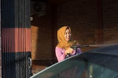 Portrait of happy hijab women car cleaning - Removing the soap with water, using a garden hose and a spray gun. Portrait of happy hijab woman doing car cleaning stock images
