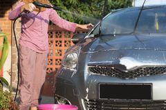 Portrait of happy hijab women car cleaning - Removing the soap with water, using a garden hose and a spray gun. Portrait of happy hijab woman doing car cleaning stock photo