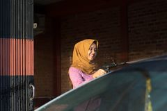 Portrait of happy hijab women car cleaning - Removing the soap with water, using a garden hose and a spray gun. Portrait of happy hijab woman doing car cleaning royalty free stock photo