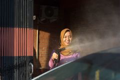 Portrait of happy hijab women car cleaning - Removing the soap with water, using a garden hose and a spray gun. Portrait of happy hijab woman doing car cleaning stock photography