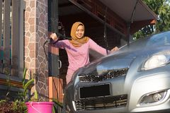 Portrait of happy hijab women car cleaning - Removing the soap with water, using a garden hose and a spray gun. Portrait of happy hijab woman doing car cleaning royalty free stock image