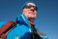 Portrait of happy hiker in sunglasses on background of blue sky Stock Images