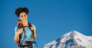 Portrait of happy hipster carrying backpack and camera standing against mountain stock photos