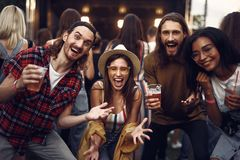 Group of cheerful young people with drinks having fun at outdoor concert stock photography