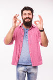 Portrait of a happy hipster man with beard showing ok sign with fingers Royalty Free Stock Photos