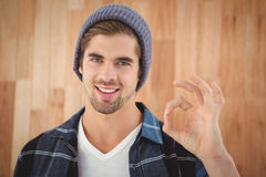 Portrait of happy hipster showing OK sign. Against wooden wall in office stock photo