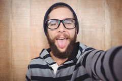 Portrait of happy hipster sticking out tongue. Against wooden wall Stock Photography
