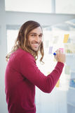 Portrait of happy hipster writing on sticky note Stock Photo