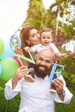 Portrait of happy hispanic family. Three people, Beard father with small son and mother on shoulders Royalty Free Stock Photos