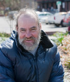 Happy homeless man. Portrait of happy homeless man outdoors during the day royalty free stock photos