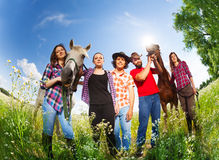 Portrait of happy horseback riders with two horses. Bottom view portrait of five happy horseback riders, standing in summer meadow with their horses Stock Images