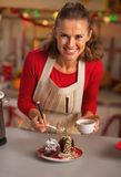 Portrait of happy housewife decorating apple in chocolate glaze. Portrait of happy young housewife decorating apple in chocolate glaze in christmas decorated Stock Images