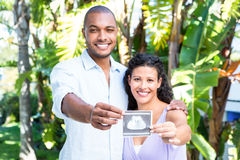 Portrait of happy husband with pregnant wife holding sonogram. Against white background Royalty Free Stock Image