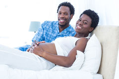 Portrait of happy husband touching belly of wife Stock Image