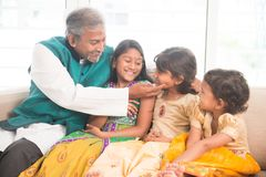 Happy father and daughters playing. Portrait of happy Indian family sitting at home. Asian father and children indoors lifestyle Royalty Free Stock Photography