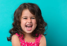 Portrait of happy, ittle girl. Happy energetic little girl on red pointing fresh. Candid portrait of cheering beautiful young white Caucasian woman on cyan Stock Photography