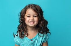 Portrait of happy, ittle girl. Portrait of a happy, positive, smiling, little girl, blue background Royalty Free Stock Photos