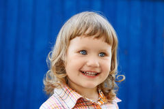 Portrait of happy joyful beautiful little girl against the blue Royalty Free Stock Photo