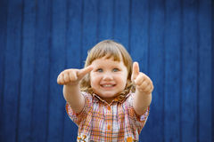 Portrait of happy joyful beautiful little girl gesturing thumb Royalty Free Stock Images