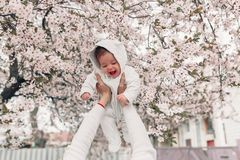 Portrait of happy joyful child in white clothes over tree flowers blossom background. stock image