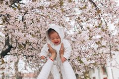 Portrait of happy joyful child in white clothes over tree flowers blossom background. Family playing together outside. Mom stock photo