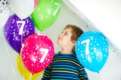 Portrait of happy kid boy with bunch on colorful air balloons on 7 birthday. Smiling school child having fun, celebrating seventh birth day. Family and best royalty free stock photography