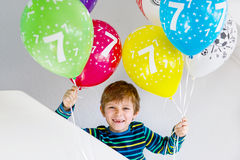 Portrait of happy kid boy with bunch on colorful air balloons on 7 birthday Royalty Free Stock Photo