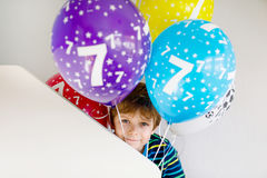 Portrait of happy kid boy with bunch on colorful air balloons on 7 birthday Royalty Free Stock Image