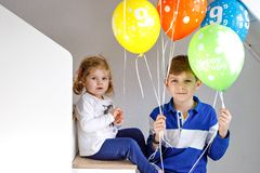 Portrait of happy kid boy and cute little toddler girl with bunch on colorful air balloons on birthday. Smiling happy stock image