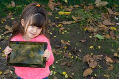 Portrait of happy kid holding tablet with both hands, showing it at camera while looking at screen with interested expression, sta. Nding outdoor. Marketing stock photo