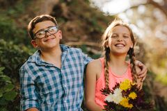 Portrait of happy kids in love sitting in park royalty free stock photo