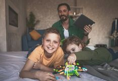 Glad father spending time with children. Portrait of happy kids playing with outgoing dad in toys. He keeping gadget in arm Stock Images