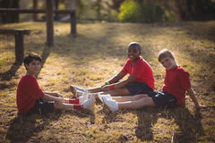 Portrait of happy kids relaxing on grass during obstacle course. In boot camp stock image