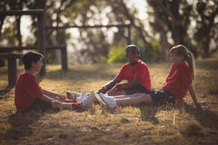 Portrait of happy kids relaxing on grass during obstacle course. Happy kids relaxing on grass during obstacle course in boot camp royalty free stock photos