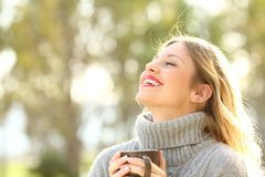 Happy lady breathing fresh air in winter. Portrait of a happy lady wearing a grey jersey breathing fresh air holding a cup of coffee in a park in winter royalty free stock photo