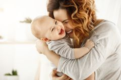 Portrait of happy laughing baby hugging with cheerful young smiling mother. Scene of pure love and happiness. Family Royalty Free Stock Photo