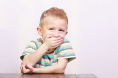 Portrait of happy laughing blond boy child kid at the table Royalty Free Stock Photos