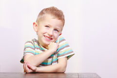 Portrait of happy laughing blond boy child kid at the table Stock Images