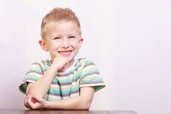 Portrait of happy laughing blond boy child kid at the table Stock Photos