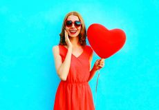 Portrait happy laughing woman holds an air balloon in the shape of a heart. On blue background Stock Photo