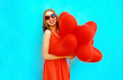 Portrait happy laughing woman with red an air balloons. On a blue background Stock Photo