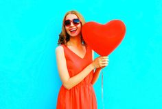 Portrait happy laughing woman in red dress, a balloon in the shape of a heart. On blue background Royalty Free Stock Photography