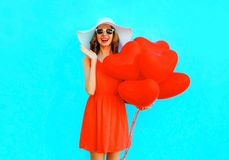 Portrait happy laughing woman in red dress, hat, with an air balloons. On a blue background Royalty Free Stock Image