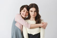 Portrait of happy lesbian girl with short hair hugging her grumpy girlfriend for photo on university party. Love and. Relationship royalty free stock photography